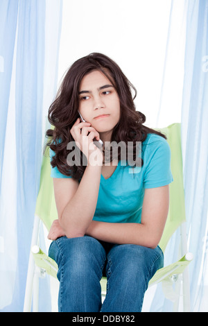 Teen girl or young woman having stressful phone conversation - Stock Photo
