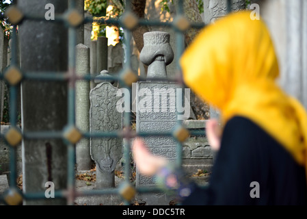 veiled woman praying in front of the old tombstones - Stock Photo