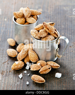 Roasted salted almonds on wooden background - Stock Photo