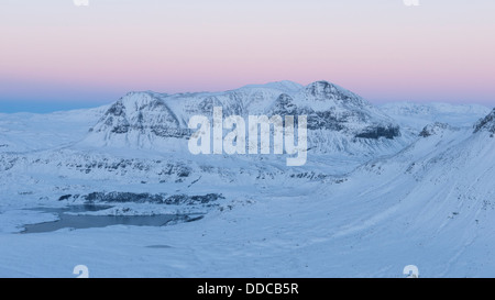 The view towards snow- covered Cul Mor from Sgorr Tuath with beautiful post sunset colours, Scottish Highlands, - Stock Photo
