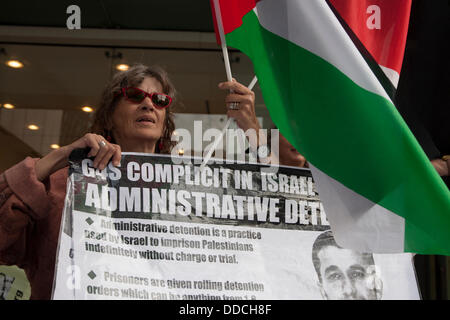 London, UK. 30th Aug, 2013.  An activist holds up a banner accusing G4S of complicity in Israeli torture as a small - Stock Photo