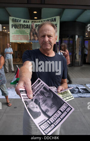 London, UK. 30th Aug, 2013.  A protester offers a leaflet highlighting the plight of Palestinian women prisoners - Stock Photo