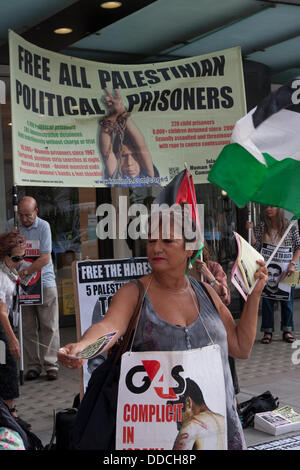London, UK. 30th Aug, 2013.  A woman hands out leaflets as a small group of activists demonstrated against G4S' - Stock Photo