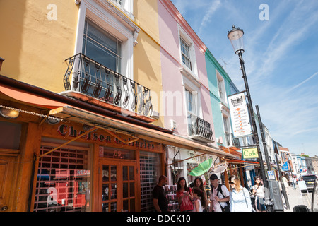 Portobello Road, London, England, pedestrians and shoppers walk the street below the famous pastel colored shops. - Stock Photo