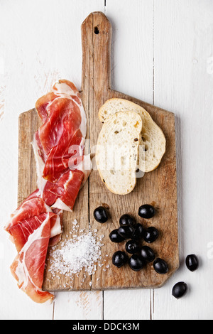 Slices of ham, Black olives and ciabatta on wooden background - Stock Photo