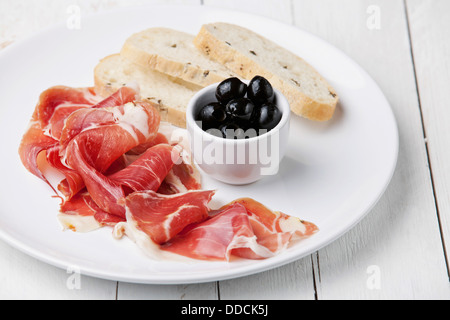 Slices of ham, Black olives and ciabatta on white plate - Stock Photo