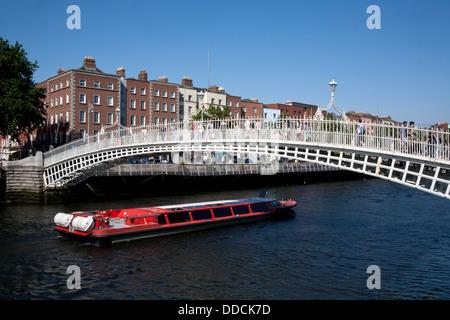 Georgian buildings along the River Liffey with a boat going under the Ha'penny Bridge, Dublin Ireland - Stock Photo