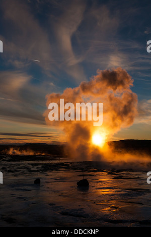 Low winter sun shines through the last gasp of steam at Geysir, Iceland - Stock Photo
