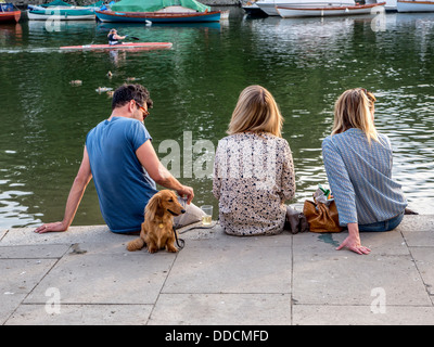 A man, two woman and a dog sitting on the banks of the river Thames - Stock Photo