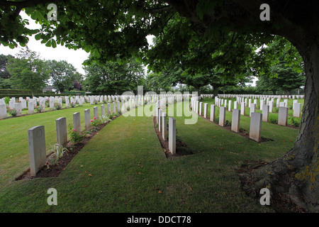 Ranks of Gravestones in a curve under trees in the British cemetery, Bayeux, Normandy France - Stock Photo