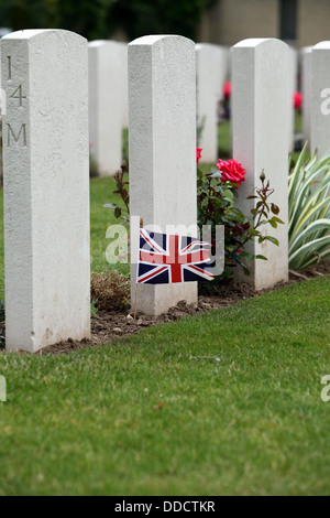 British flag flying at the base of a grave in the British Cemetery, Bayeux, Normandy, France - Stock Photo
