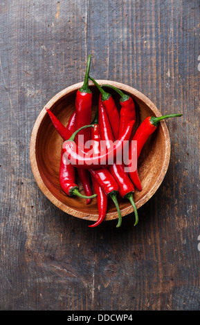 Red Hot Chili Peppers in wooden bowl on old wooden background - Stock Photo