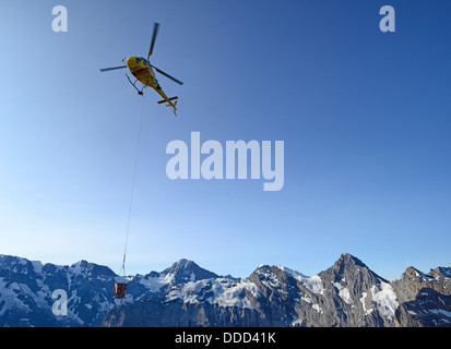 Air Glacier Helicopter delivering construction materials to Schilthorn, Piz Gloria, Swiss Alps, Switzerland, Europe - Stock Photo
