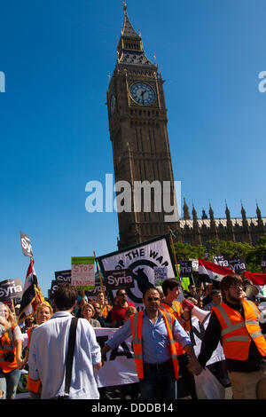 London, UK. 31st Aug, 2013.  Protesters pass Parliament as thousands march against US and other western countries - Stock Photo