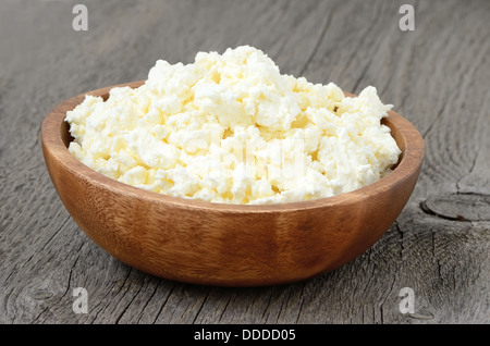Cottage cheese in the bowl on the wooden garden table - Stock Photo