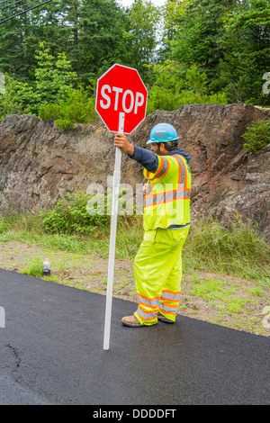 A flagman, dressed in bright yellow-green clothing holds a traffic sign to stop cars down during a road construction - Stock Photo