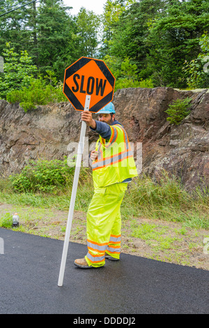 A flagman, dressed in bright yellow-green clothing holds a traffic sign to slow cars down during a road construction - Stock Photo