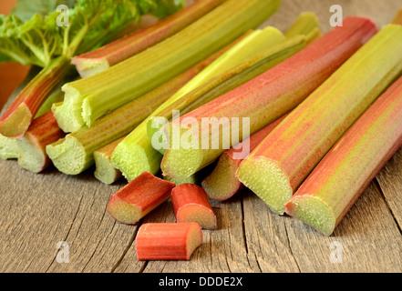 Fresh rhubarb on wooden garden table - Stock Photo