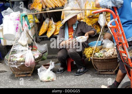 Food seller preparing food for customer on street in Bangkok , Thailand - Stock Photo