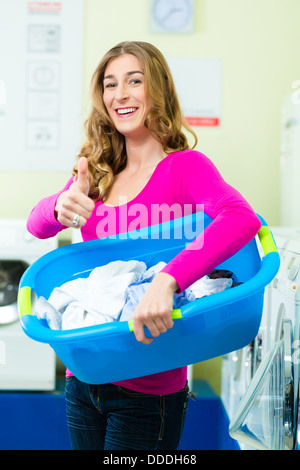 Young woman with laundry basket in a laundrette she washed their laundry clean and is happy about it - Stock Photo