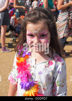 Young girl with her face painted and wearing a garland of flowers at a summer festival - Stock Photo