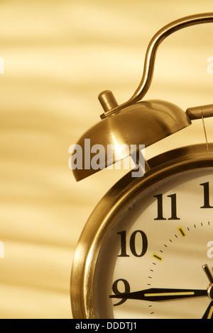 Early morning light casting upon analog alarm clock. - Stock Photo