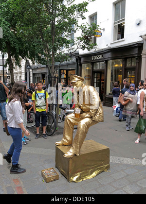 Street performer busker dressed in gold sitting on an invisible chair in Covent Garden, London - Stock Photo