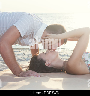 Beautiful couple lying down and kissing on the beach. guy kisses on top - Stock Photo