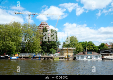 A new high quality housing and hotel development, Kingston Riverside, towers above houseboats at Kingston Upon Thames. - Stock Photo