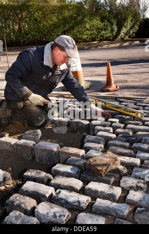 self building house, hard landscaping, workman laying reclaimed granite setts at entrance to driveway - Stock Photo