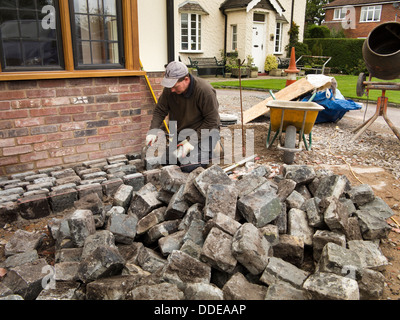 self building house, hard landscaping, workman laying reclaimed granite setts around new build home - Stock Photo