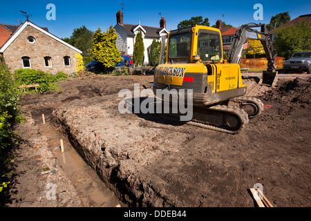 Al844 self building house, preparing site, volvo digger digging trench for foundations - Stock Photo
