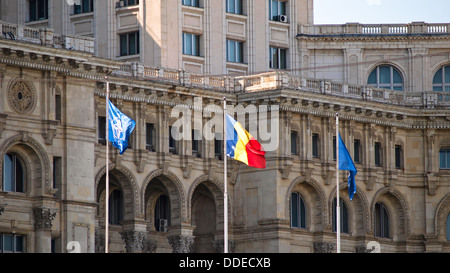 Romanian flag, along with NATO and European Union flags, in front of the Palace of Parliament. - Stock Photo