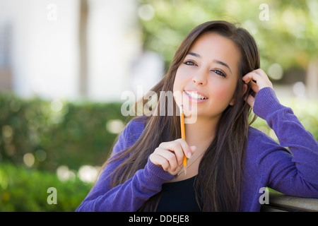 Attractive Pensive Mixed Race Female Student with Pencil Sitting on Campus Bench. - Stock Photo