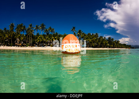 A marker buoy on the surface of a calm tropical sea as SCUBA divers train below - Stock Photo