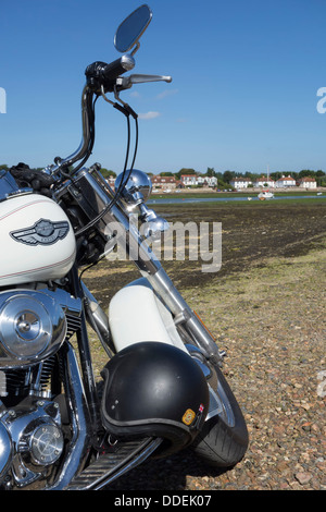 Detail showing the front end of a harley davidson softail motorcycle parked on a beach at low tide  ( editorial - Stock Photo