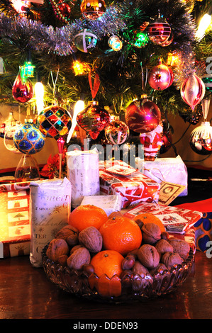 Glass bowl filled with walnuts, hazelnuts and mandarin oranges with Christmas presents under tree to the rear. - Stock Photo