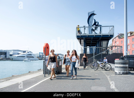 People girls women walking along Poole Quay Dorset UK with viewing platform in background with blue sky behind - Stock Photo