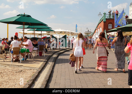 Cafes and people on Brighton seafront beach and promenade East Sussex England UK - Stock Photo