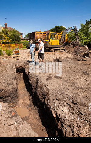 self building house, preparing site, workers inspecting trench dug for foundations by volvo digger - Stock Photo