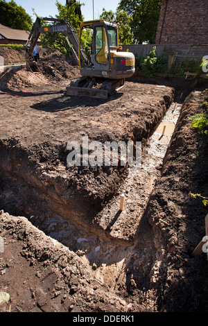 self building house, volvo digger preparing site after concrete foundations, have been poured - Stock Photo