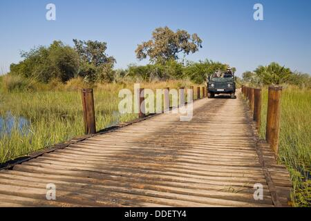 A safari vehicle driving over a wooden bridge in the Okavango Delta in Botswana, Africa - Stock Photo
