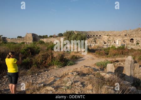 A tourist takes a photograph of the Roman Amphitheatre, Side, Turkey. - Stock Photo