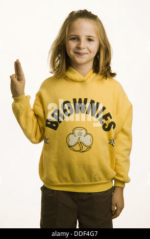 10 year old girl dressed in her Brownies uniform giving the three fingered salute - Stock Photo
