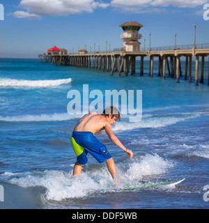 Boy surfer surfing waves on Huntington beach pier California - Stock Photo