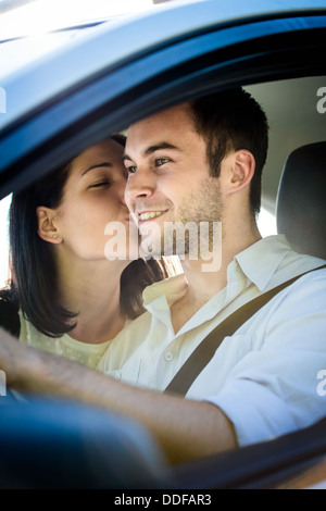 Couple in car - young woman kissing man in car while driving - Stock Photo