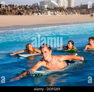 Teenager surfer group boys and girls swimming over the surfboard in santa monica california - Stock Photo