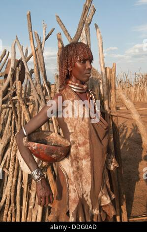 Young Hamar woman with red clay in her hair and wearing a goat dress, Omo river valley, Southern Ethiopia - Stock Photo