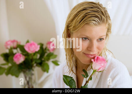 Woman smelling a flower - Stock Photo
