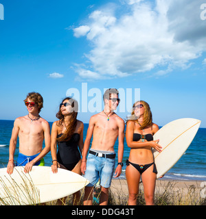 Boys and girls teen surfers happy smiling over dune beach in summer - Stock Photo